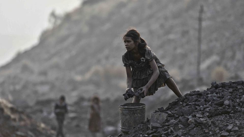 A minor picks up chunks of coal from an open-cast mine in Jharkhand.