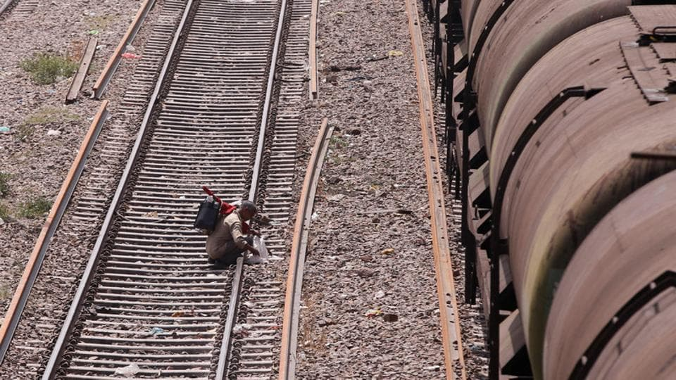 An employee checks a railway track next to a tanker wagon train at Okhla railway station in New Delhi.