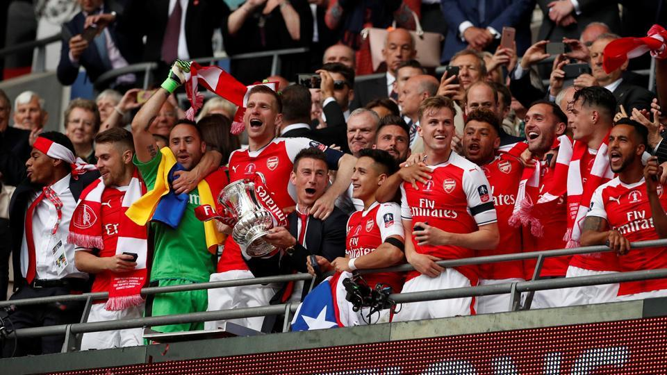 Arsenal's Laurent Koscielny (in black) and Per Mertesacker (with the Cup) lift the FA Cup and celebrate with team mates after defeating Chelsea 2-1 in the FA Cup final at Wembley on Saturday.