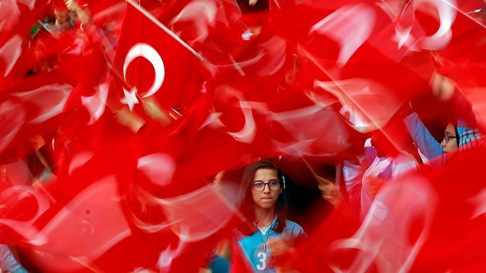 Imam Hatip religious school students wave national flags as they wait for arrival of Turkish President Tayyip Erdogan during a graduation ceremony in Istanbul, Turkey. (Murad Sezer  / REUTERS)