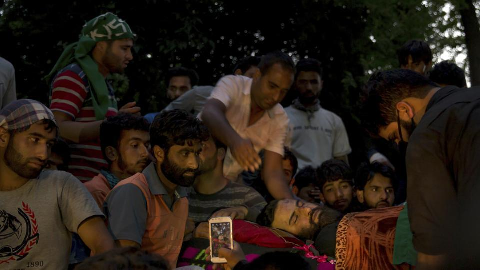 Kashmiri villagers crowd near the body of Hizbul militant Sabzar Ahmad Bhat in south Kashmir's Tral on Saturday, a few hours after he and an associate were killed  in a gunfight with security forces.