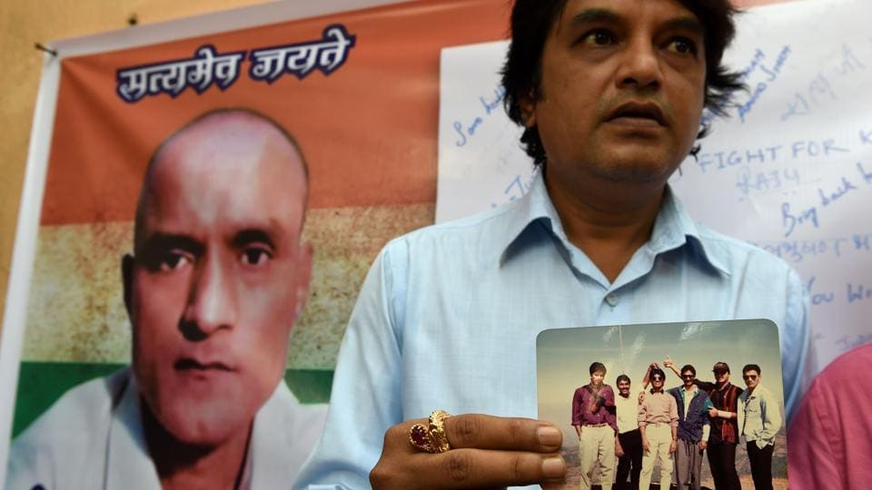 Kulbhushan Jadhav's friend holds a photograph of the Indian national who was arrested in Pakistan, in Mumbai.