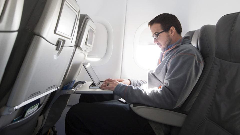 A man uses his laptop on a special JetBlue media flight out of John F. Kennedy International Airport in New York in this December 11, 2013.