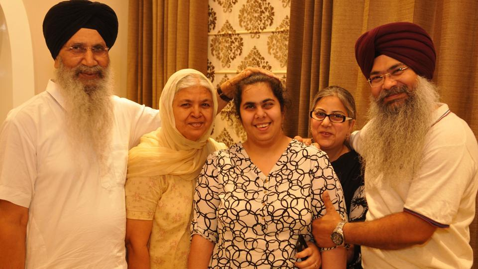 Gurleen Kaur who got 89% in her Class 12,  with her family members in Jalandhar, India on Sunday.