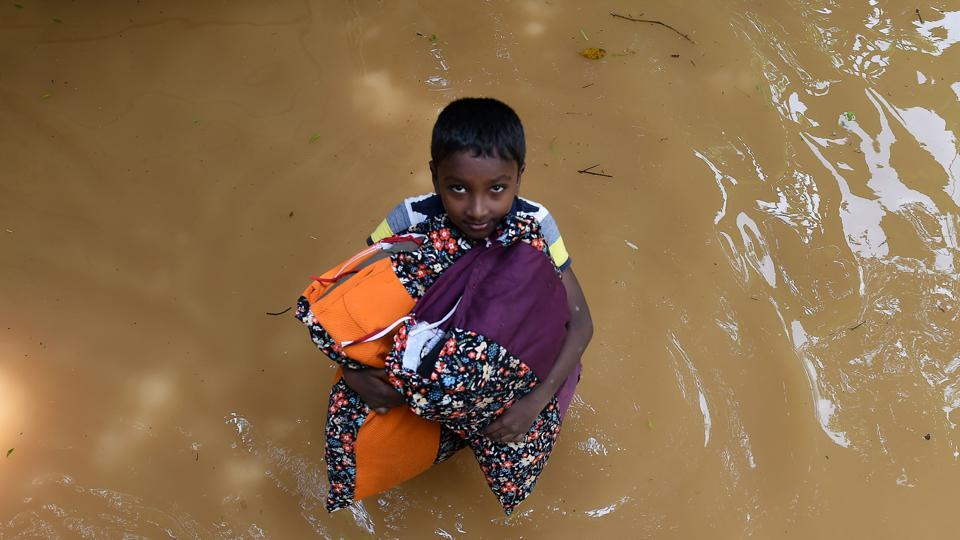 A Sri Lankan boy carries pillows through floodwaters from his home in Kelaniya on May 27, 2017.