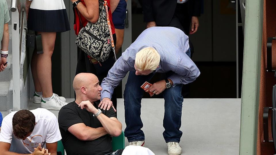Andre Agassi, coach of Novak Djokovic, speaks with Boris Becker on day two of the French Open.  (Getty Images)