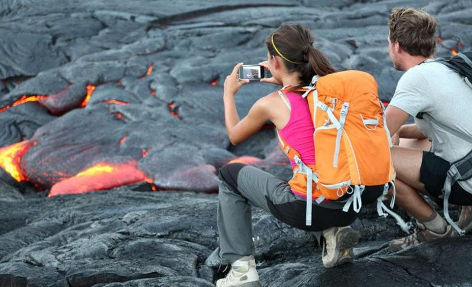 Tourists taking photo of flowing lava from Kilauea volcano around Hawaii volcanoes national park, USA.