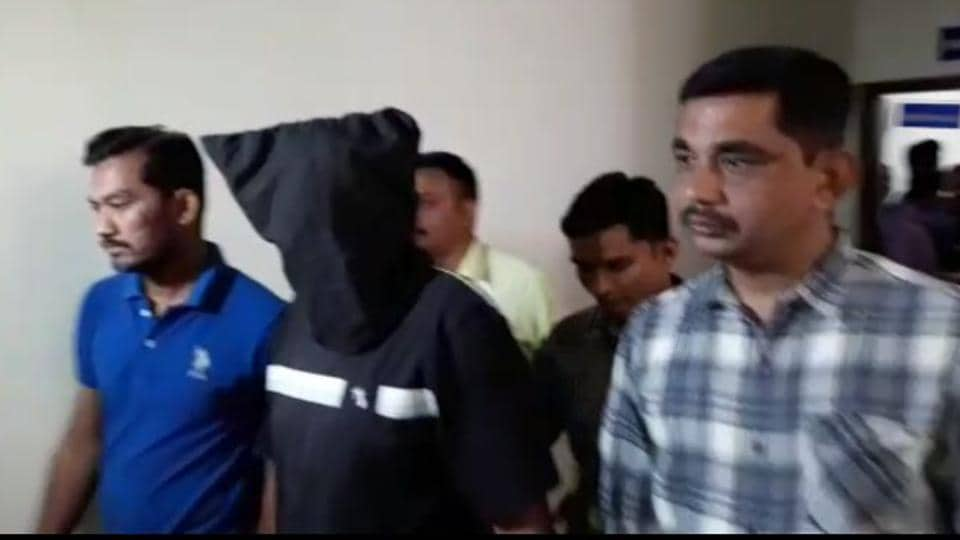 ATS personnel take one of the brothers, accused of having Islamic State links, into custody.