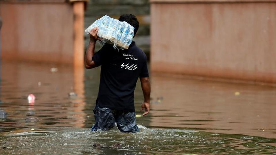 A man carries a pack of water bottles as he walks through a flooded road in Dodangoda village. Police said a Sri Lankan Air force helicopter (SLAF) MI-17 carrying relief aid for flood victims crashed in the southern Galle district, the worst hit of the 14 districts by flash floods and earth slips in the ongoing monsoon rains, while carrying out relief operations in the flooded areas. (Dinuka Liyanawatte/Reuters)