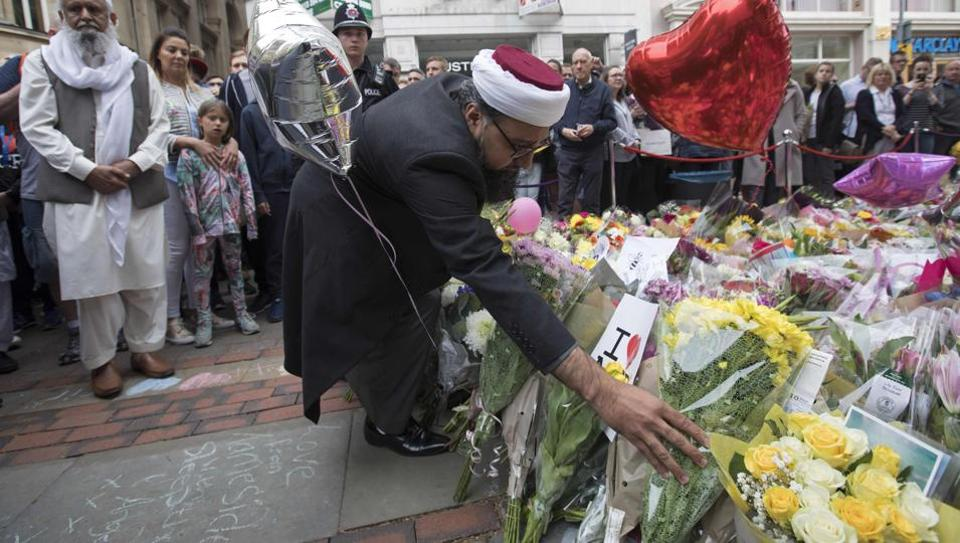 A man lays flowers for the victims of the Manchester bombing at St Ann's square in Manchester.
