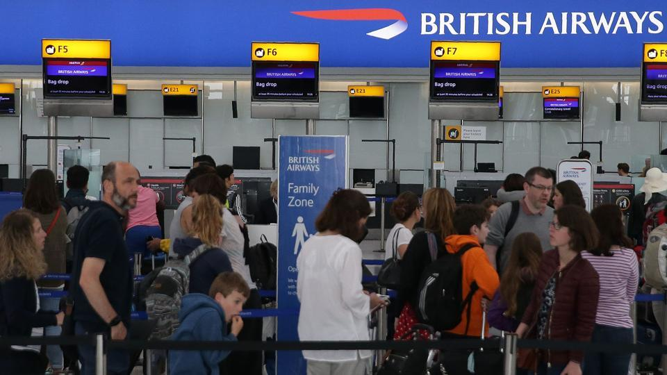 Passengers arrive with their luggage in Terminal 5 of London's Heathrow Airport on May 29, 2017. Passengers faced a third day of disruption at Heathrow Monday as British Airways cancelled short-haul flights after a global computer crash that unions blamed on the outsourcing of IT services to India.