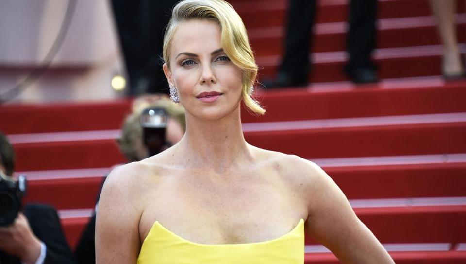 Charlize Theron poses as she arrives for the screening of the film Mad Max : Fury Road during the 68th Cannes Film Festival in Cannes on May 14, 2015.