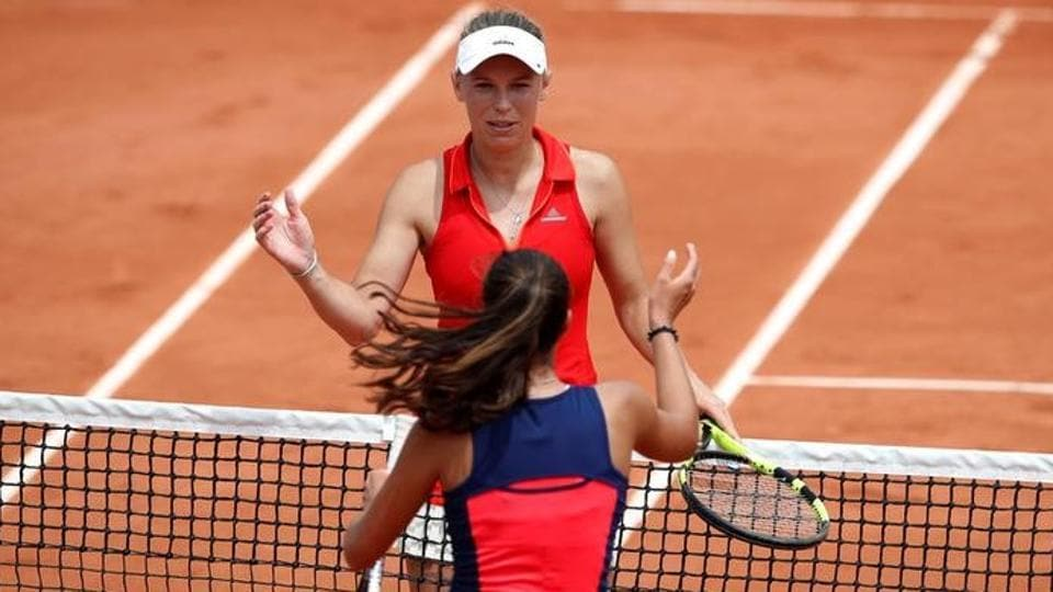 Denmark's Caroline Wozniacki celebrates winning her first round match at French Open as she shakes the hand of Australia's Jaimee Fourlis.
