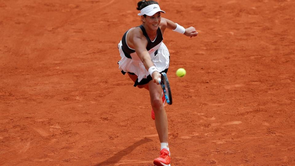 Garbine Muguruza stretches to make a return against Francesca Schiavone during their French Open first round match on Monday.