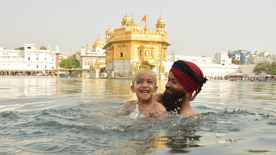 Devotees taking holy dip and paying obeisance at Golden Temple on the occasion of martyrdom anniversary of Sikh Guru Arjan Dev in Amritsar on Monday. (Gurpreet Singh/HT Photo)