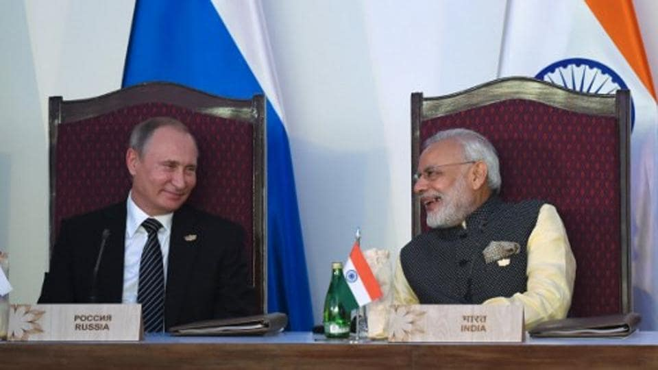 India Prime Minister Narendra Modi (R) smiles while talking with Russia's President Vladimir Putin during the BRICS leaders' meeting with the BRICS Business Council at the Taj Exotica hotel in Goa.