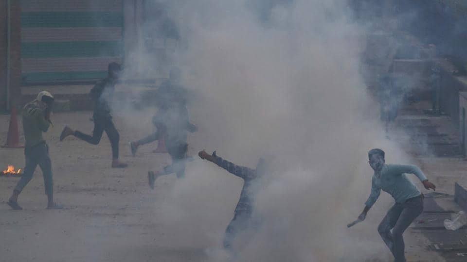 A Kashmiri protester throws an exploded tear gas shell back at police during a protest in Srinagar.