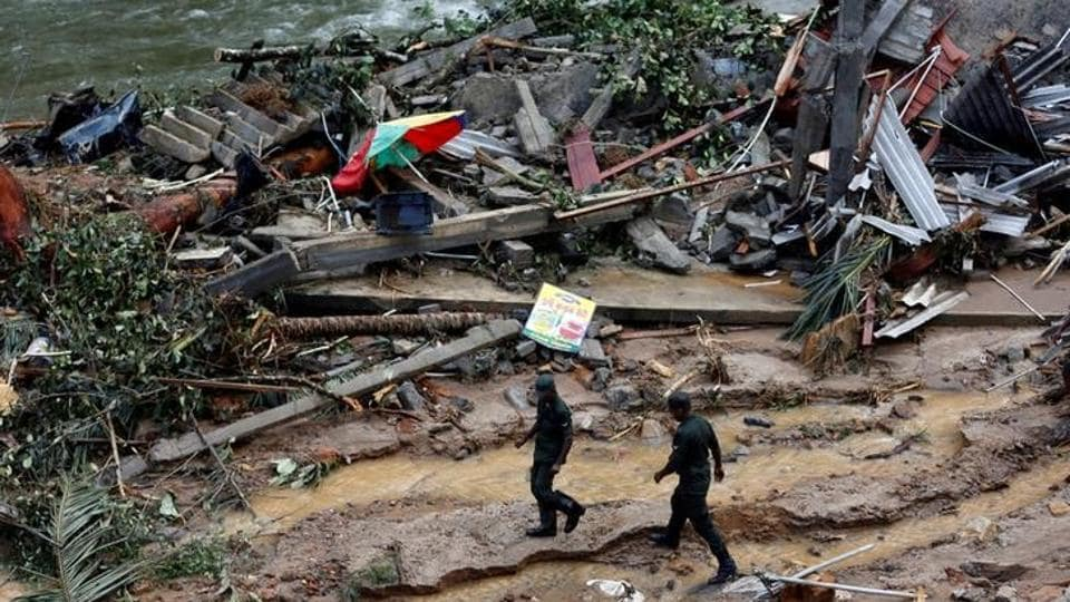 Sri Lankan army soldiers walk past the debris of houses at a landslide site. The Disaster Management Centre (DMC) said 104 people are still missing while 88 remain in hospital.  (Dinuka Liyanawatte/Reuters)