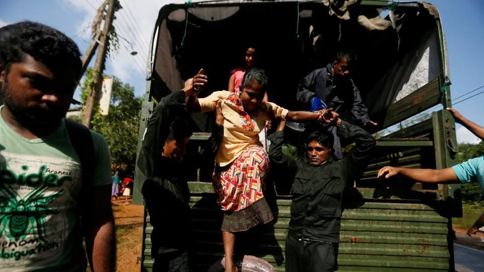 Sri Lankan army soldiers help a flood victim to get off from a truck during a rescue mission. On Saturday, a Lanka Air Force airman, YMS Yaparatne,37, died while carrying out relief operations in the Galledistrict as he fell off from the helicopter. (Dinuka Liyanawatte/Reuters)
