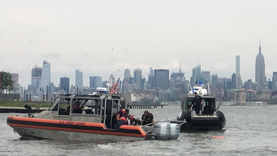 US Coast Guard crews work on a parachutist in the waters of the Morris Canal after the skydiver's chute failed to open during an aerial exhibition as port of New York Harbor's Fleet Week festival in New York City.