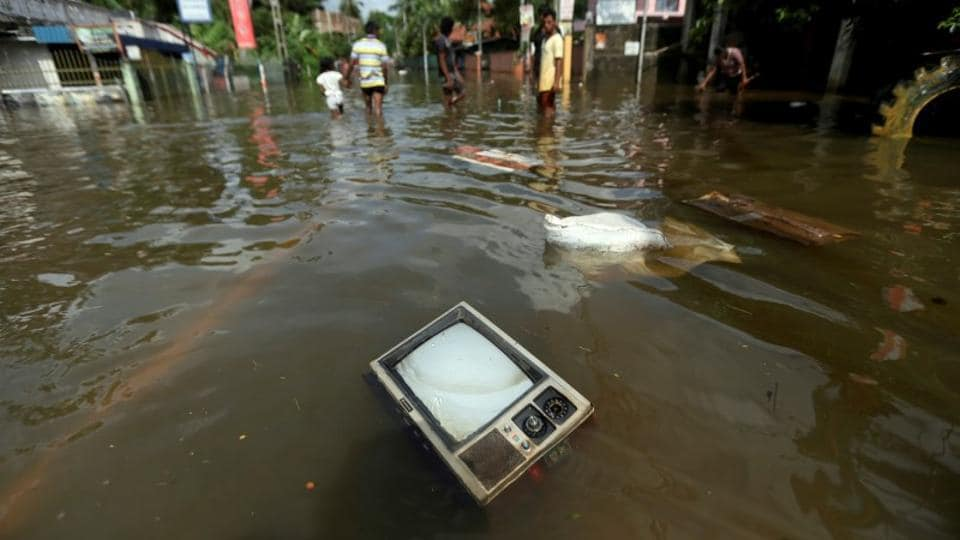 A TV set floats on a flooded road in Dodangoda village in Kalutara. Rescuers in Sri Lanka today pulled out more bodies buried in the mudslides triggered by the country's worst torrential rains in 14 years, taking the death toll to 164. (Dinuka Liyanawatte/Reuters)
