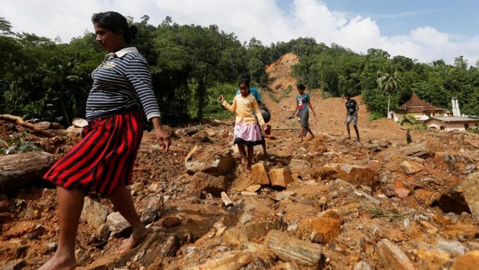 People walk through a landslide site during a rescue mission. There were no casualties in the crash and Sri Lankan President Maithripala Sirisena telephoned the Squadron Leader Bhanuka Delgoda, the pilot of the MI-17 to congratulate him for his bravery. (Dinuka Liyanawatte/Reuters)