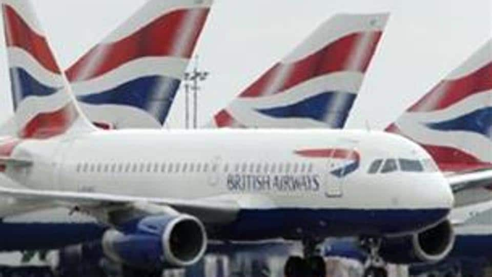 British Airways passenger jet taxis past parked BA jets at Heathrow airport in London.