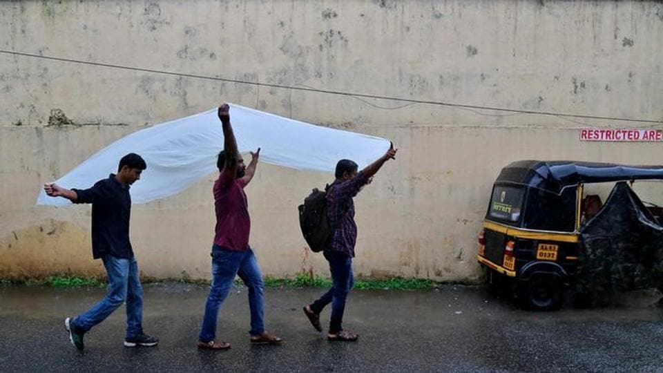 Men use a plastic sheet to cover from rain as they walk along a road in Kochi.  (Sivaram V/Reuters)