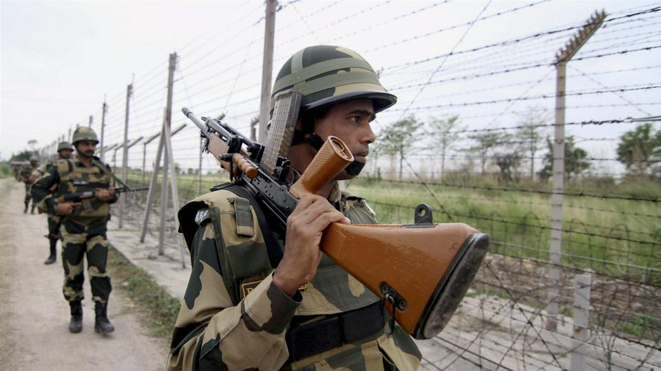 A BSF jawan patrolls the International Border on the outskirts of Jammu.
