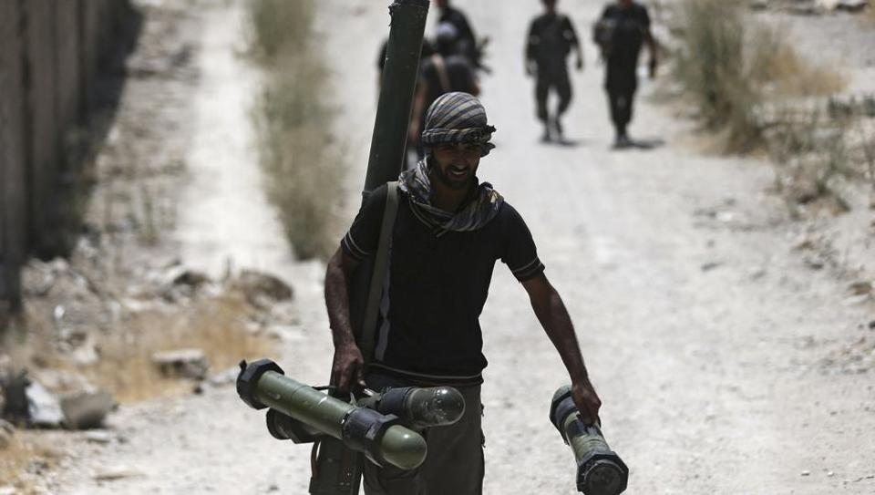 A fighter from the Free Syrian Army's Al Rahman legion carries a weapon as he walks towards his position on the frontline against the forces of Syria's President Bashar al-Assad in Jobar, a suburb of Damascus,
