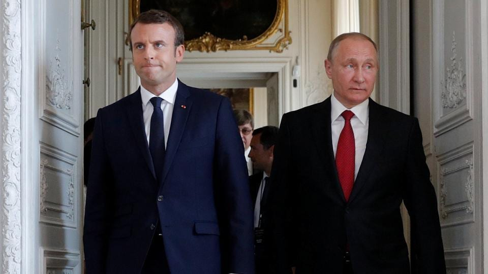 French President Emmanuel Macron (left) walks with Russian President Vladimir Putin at the Chateau de Versailles in Versailles, France.