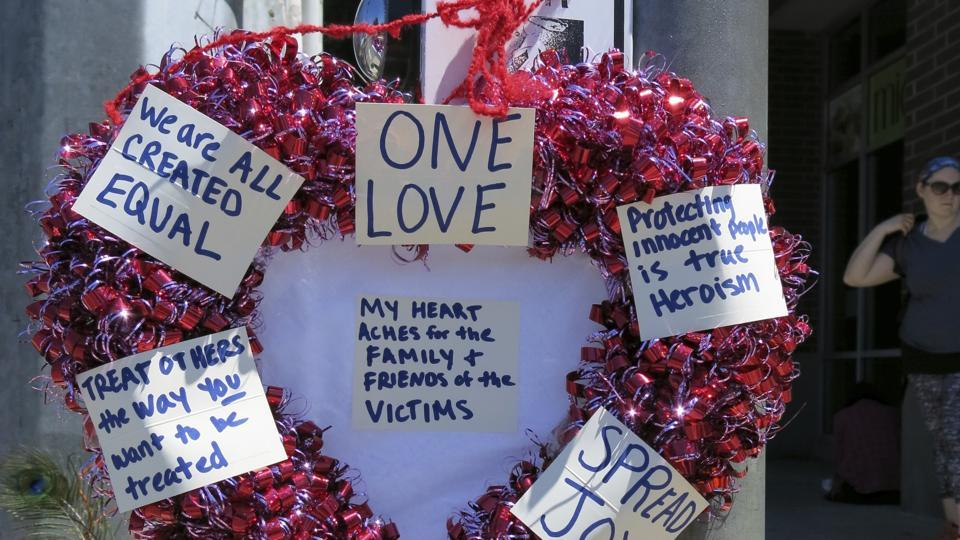 A heart-shaped wreath hangs on a traffic light pole at a memorial for two bystanders who were stabbed to death Friday, while trying to stop a man who was yelling anti-Muslim slurs and acting aggressively toward two young women, including one wearing a Muslim head covering, on a light-trail train in Portland, Ore, Saturday, May 27, 2017.