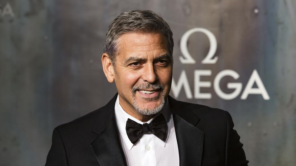 George Clooney poses for photographers upon arrival at the party being held for the 60th anniversary of the Omega Speedster watch in London.