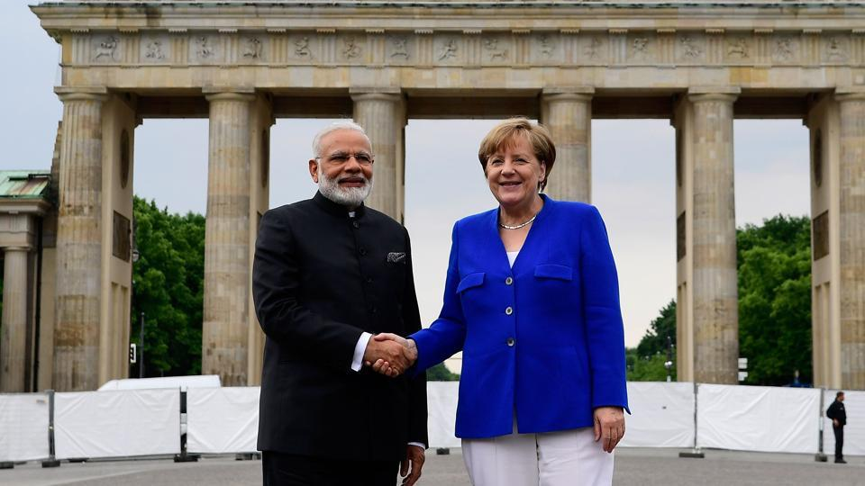 Prime Minister Narendra Modi with German chancellor Angela Merkel in front of the Brandenburg Gate in Berlin on Tuesday.