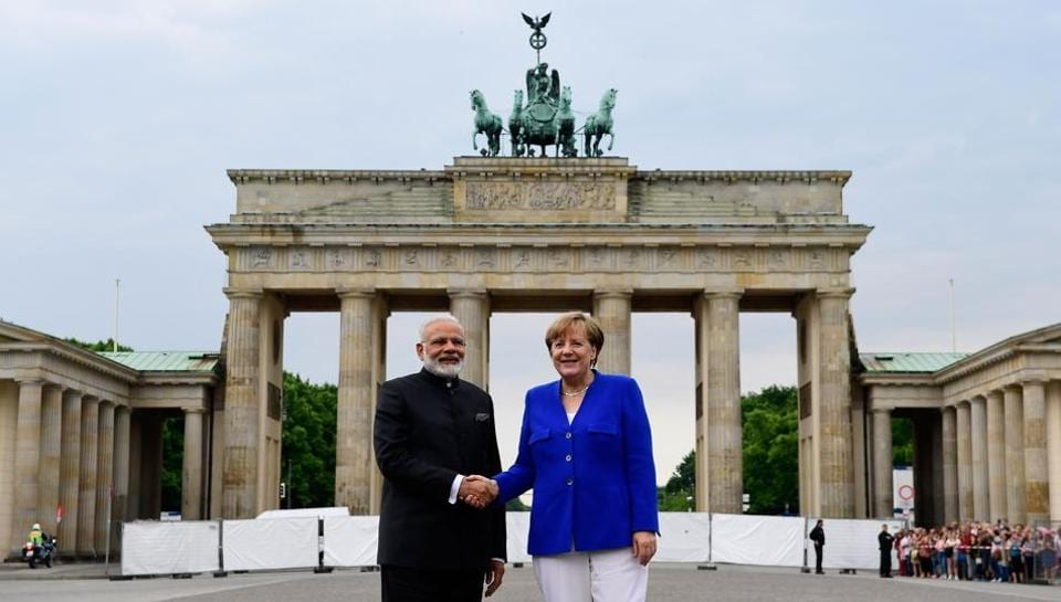 German Chancellor Angela Merkel shakes hands with Indian Prime Minister Narendra Modi in front of the Brandenburg Gate in Berlin on May 30, 2017.