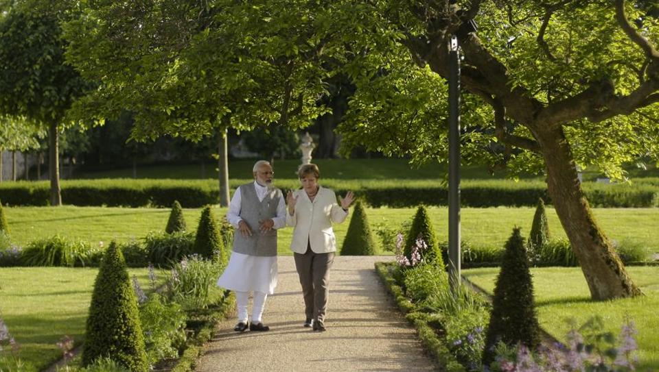 German Chancellor Angela Merkel, right, and Prime Minister Narendra Modi, walk through the garden of the government guest house Meseberg Palace during a meeting in Meseberg.
