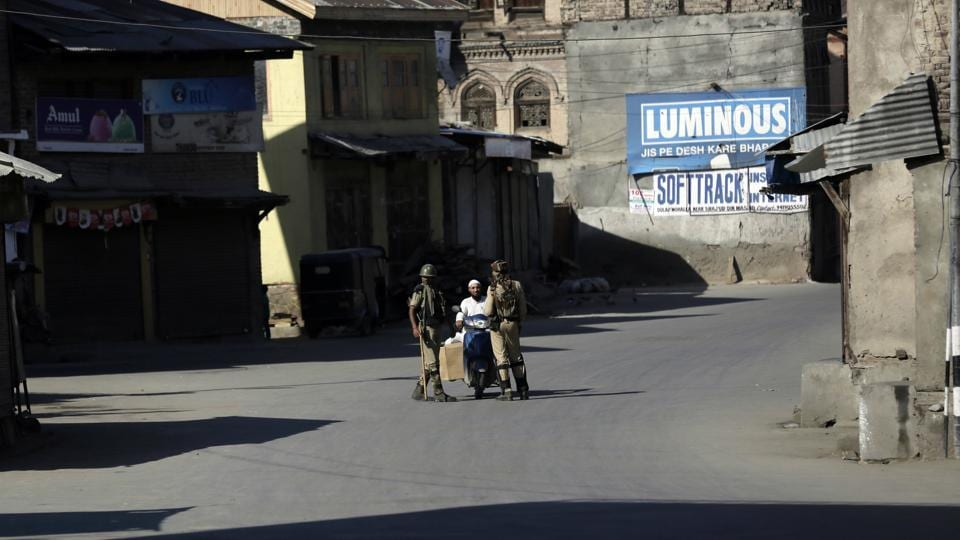 Soldiers question a man on a motorcycle at a temporary checkpoint during restrictions in Srinagar on Monday.