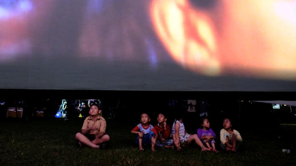 Children sit in a soccer field watching films, during a wedding party in Tangerang.  (REUTERS)