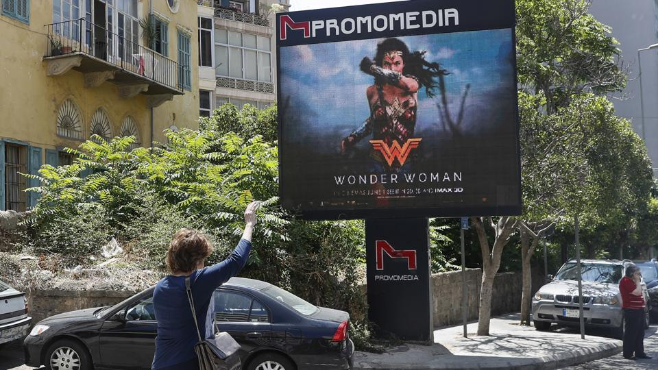 A Lebanese woman waves for a taxi as she stands in front of a digital billboard promoting the Wonder Woman movie in Beirut, Lebanon, on May 30, 2017.