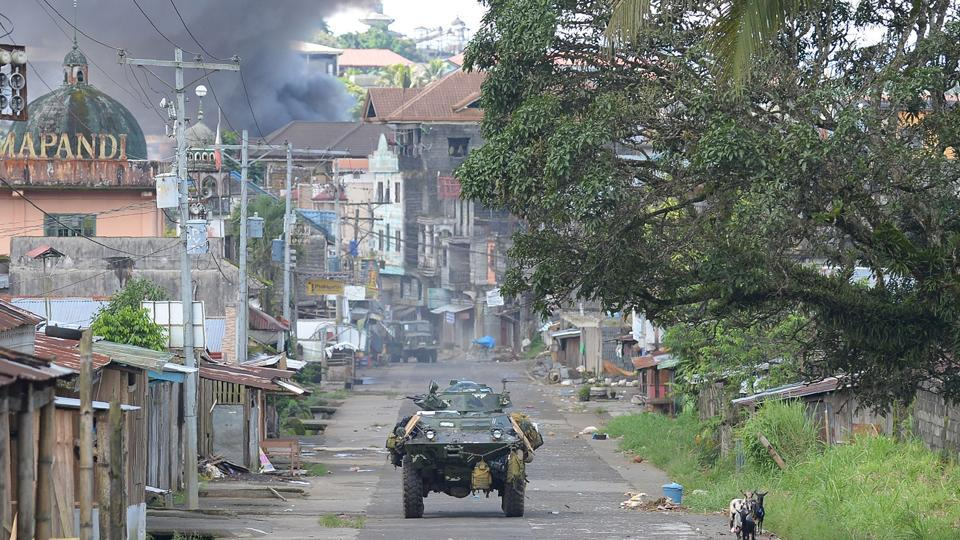 A Philippine Marines armoured personnel carrier speeds away as black smoke billows from burning houses after military helicopters fired rockets at militant positions in Marawi on the southern island of Mindanao.