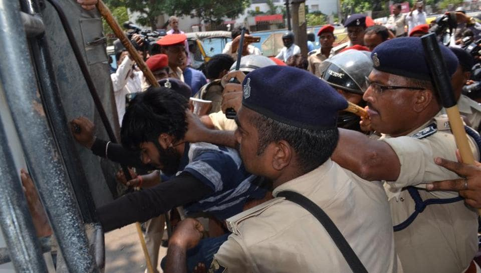 Policemen prevent students trying to force open the gate of the Bihar School Examination Board in Patna on Wednesday.