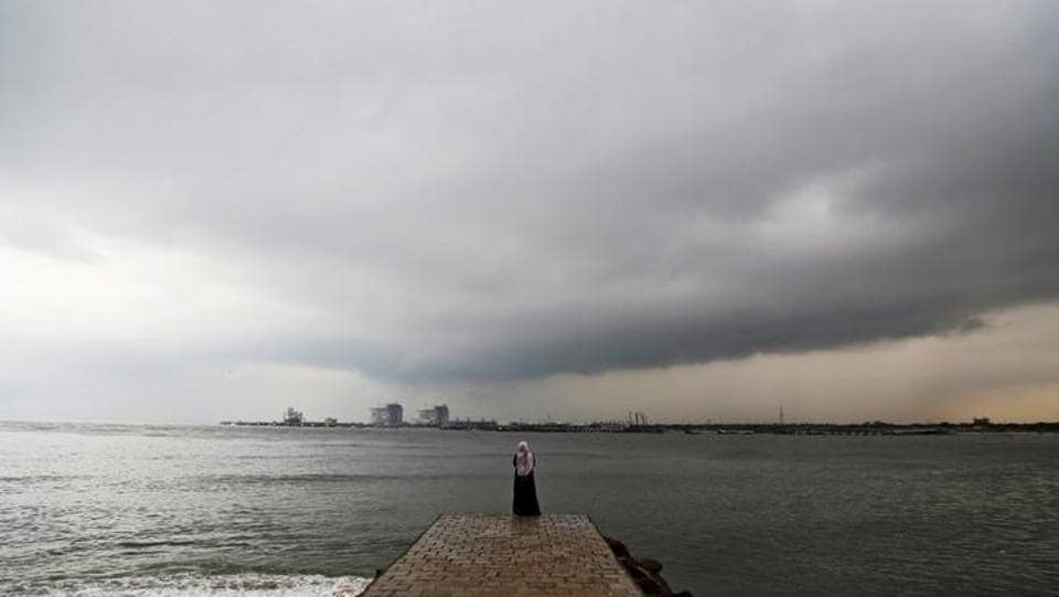 A woman stands on a seaside promenade against the background of pre-monsoon clouds gathered over the Arabian Sea in Kochi.  (Sivaram V/Reuters)