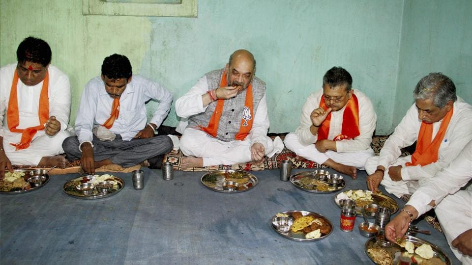 BJP president Amit Shah and other leaders have a meal at a tribal's house in Devaliya village in Gujarat on Wednesday.