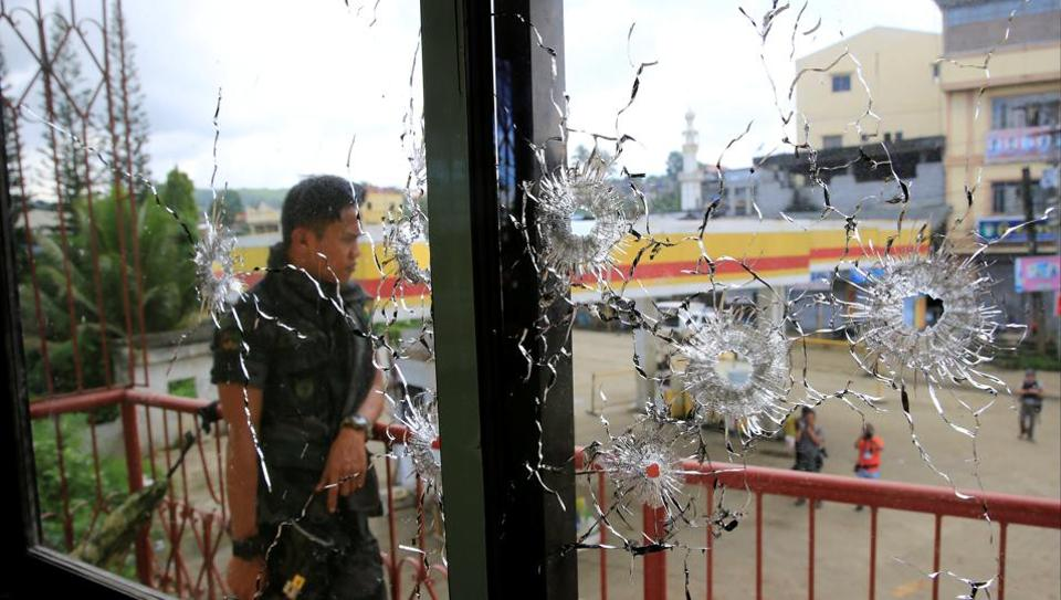 A policeman stands on guard behind a window full of bullet holes in Marawi city, Philippines.