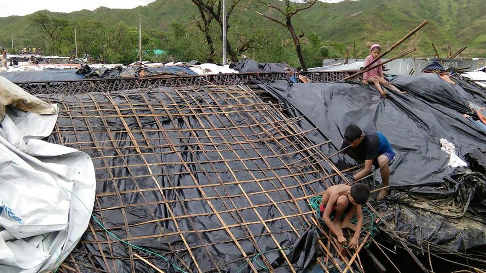 Rohingya refugee children fix the damaged roof of a hut in a makeshift camp in Bangladesh's Cox's Bazar district after Cyclone Mora made landfall in the region.