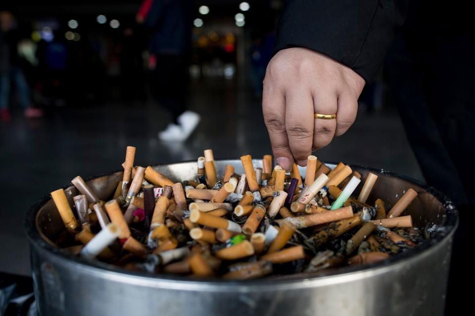 A man grinding out his cigarette in an ashtray at a railway station in Shanghai. Smoking-related diseases claim 7 millions of lives each year in the world, the World Health Organization reported on May 30, 2017, calling to increase taxes on tobacco. (JOHANNES EISELE / AFP)