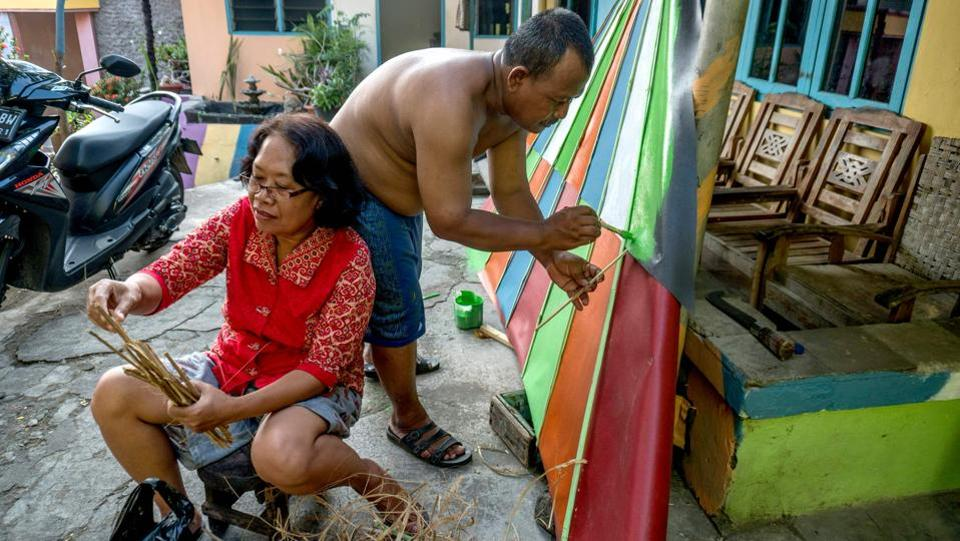 Villagers painting part of their homes following a major makeover of their Indonesian hamlet dubbed 'the rainbow village'in Semarang, central Java. (SURYO WIBOWO / AFP)