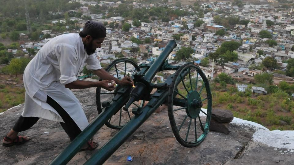 A man lights a cannon on top of the Raisen fort hill. About 40 kms from Bhopal, the residents of Raisen town still follow an age old tradition which involves firing a cannon to signal the locals for Sehri and Iftar during the holy month of Ramzan. First started almost 250 years ago by the Nawabs, it is followed with much ardour by the youths, generation after generation.  (Mujeeb Faruqui/HT Photo)