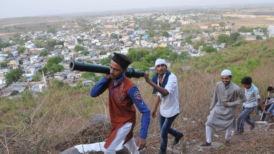 Youths belonging to Muslim Teohar committee carry the cannon to top of the hill. During the whole month of Ramzan,the cannon is fired twice a day to mark the simultaneous  commencement and completion of fast.   (Mujeeb Faruqui/HT Photo)