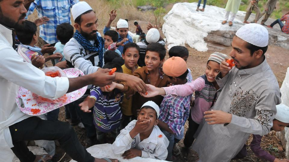 Youths distribute sweets after successful installation of the cannon on the top of the Raisen fort hill.  (Mujeeb Faruqui/HT Photo)